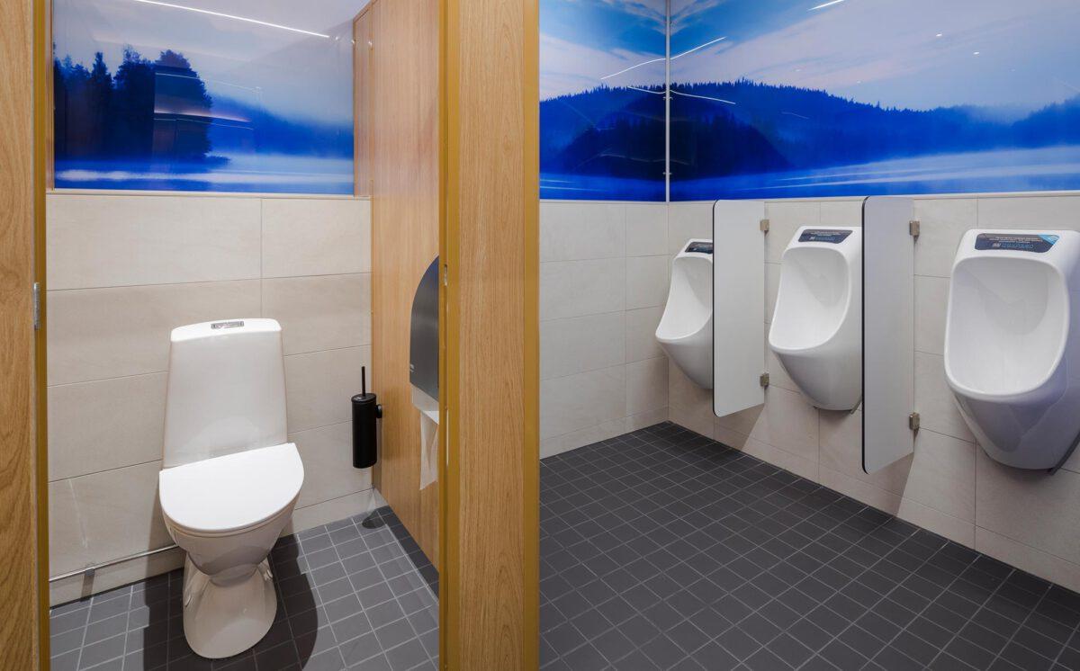 Kauppakeskus Goodman ravintolamaailma. Yksi WC-koppi, jossa on WC-istuin ja musta vessaharja. Sivuseinällä näkyy kolme valkoista urinaalia.