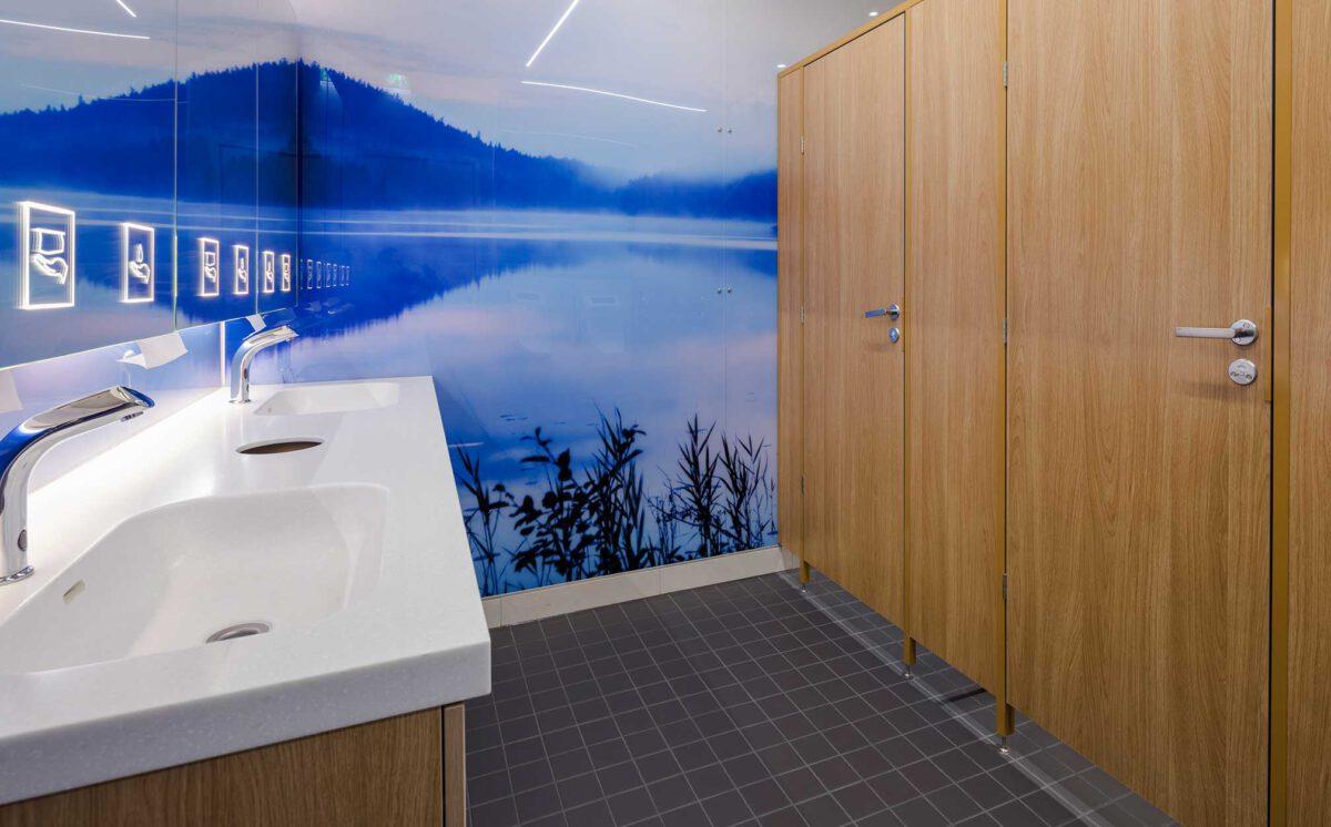 Novosan referenssi. Kauppakeskus Goodman. Sinisen sävyinen miesten vessa, kahdella käsienpesupaikalla ja WC-kopilla.