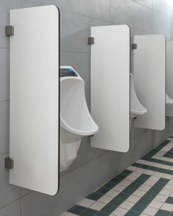 Urimat-pisuaarit ja Ujo-väliseinät kuvattuna sivulta miesten WC:ssä. Seinässä on harmaa vaaka laatoitus. Lattiassa on tummanvihreää ja valkoista lattialaattaa.