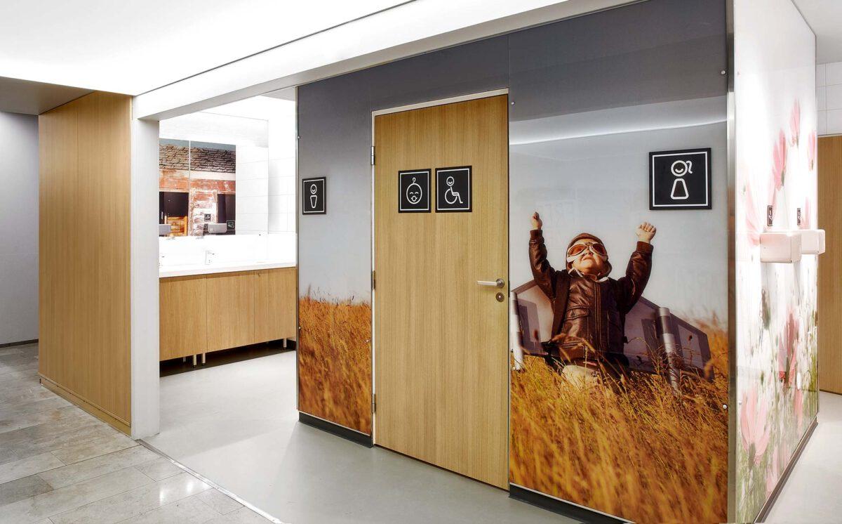 Kauppakeskus Sellon naisten vessan sisäänkäynti. Oveen ja seinään on kiinnitetty on ohjaavat mustavalkoiset WC-opasteet: Inva-WC, lastenhoitohuone, naiset ja miehet.