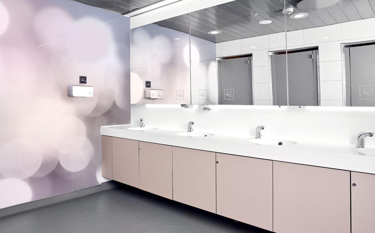 Novosan referenssi. Kauppakeskus Sellon naisten-WC. Vessassa on neljä valkoista käsienpesuallasta. WC:n allaskaapit ovat vaalean roosan väriset.