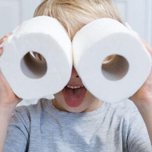 Pieni poika kiikaroi WC-paperirullilla.