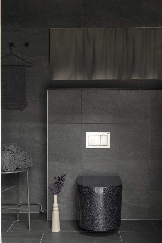 Woodio Block seinäkiinniteinen WC-istuin. Hiilenmusta seinäkiinniteinen wc-istuin mustavalkoisessa kylpyhuoneessa.