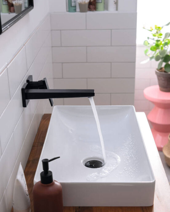 Hansgrohe Metropol-seinäallashana. Musta hana vipukahvalla on asennettu saniteettitilan seinään. Hanasta valuu vettä valkoiseen käsienpesualtaaseen.
