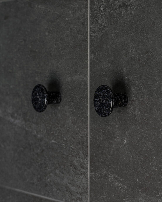 Woodio Hook -vaatekoukut. Kaksi pyöreää hiilenmustaa vaatekoukkua kuvattuna tummassa seinässä. Tuotenumero: 6438441029375.