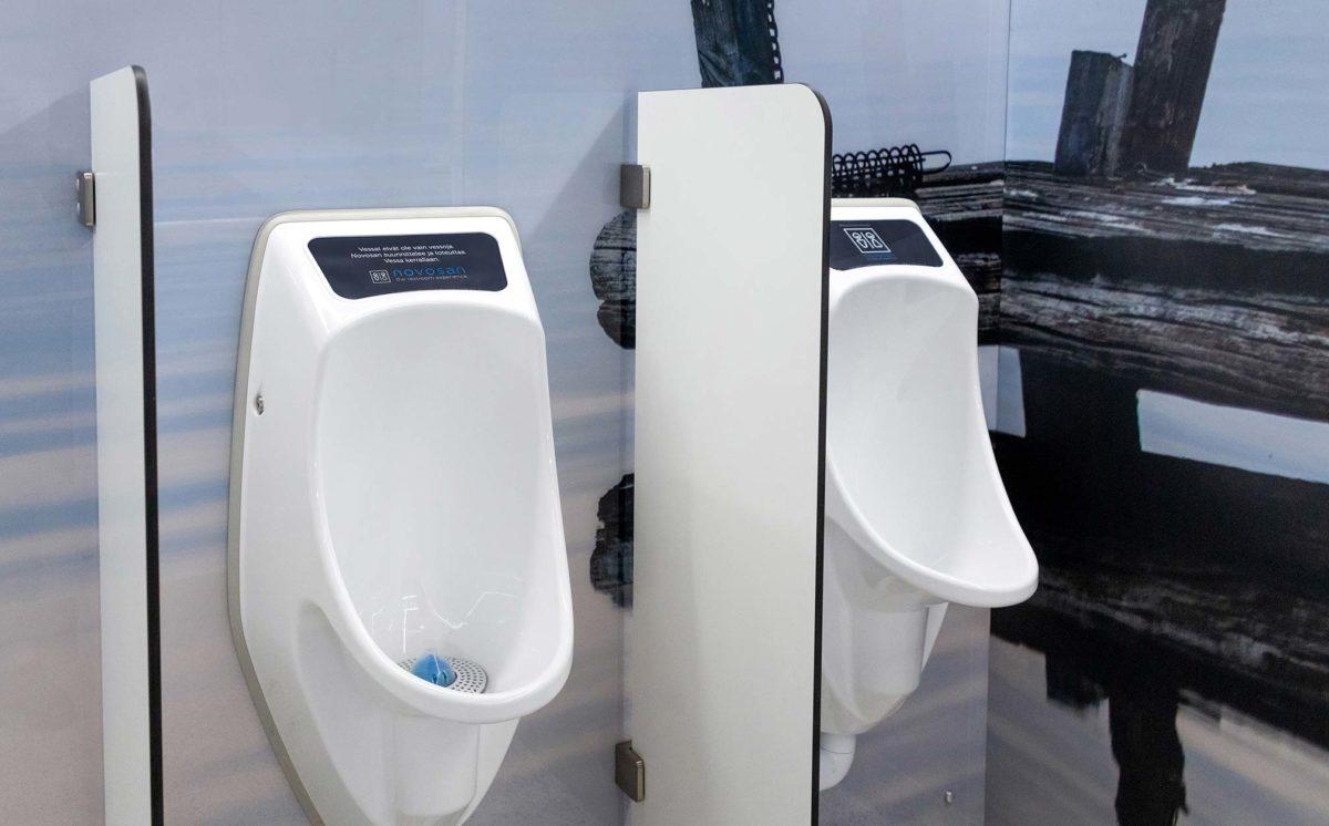 Vedettömät Urimat-pisuaarit EcoPlus ja CompactPlus miesten vessassa. Kaksi valkoista Ujo-väliseinää rajaavat sinertävää tilaa.