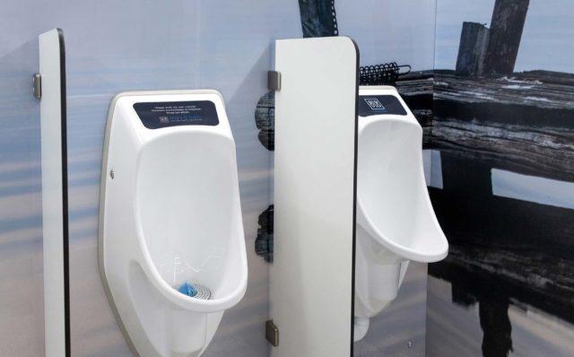 Vessakontin miesten-WC:n seinään on asennettu valkoiset Urimat-pisuaarit ja väliseinät.