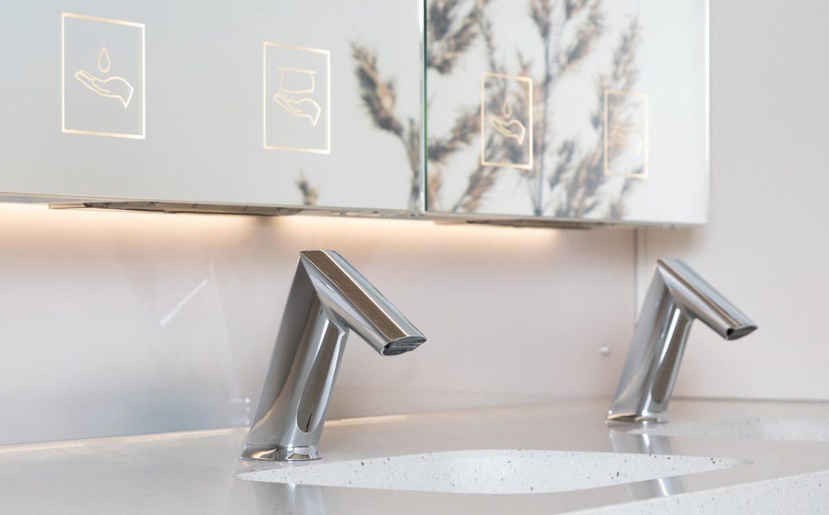 Lähikuva WC-vaunun pesualtaista. Kuvassa näkyvät: peilikaapit, valaistut opasteet, kaksi lavuaaria, ja kaksi kromista hanaa.