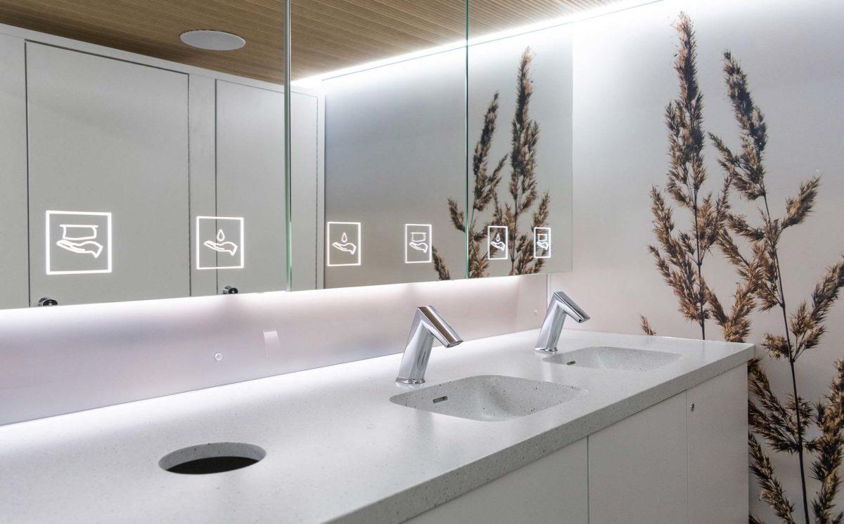 WC-vaunun sisätila. Tilassa on peilikaapit, kaksi WC-koppia, käsienpesualtaat ja kaksi kromista hanaa. Seinäpaneelissa on luontokuva.