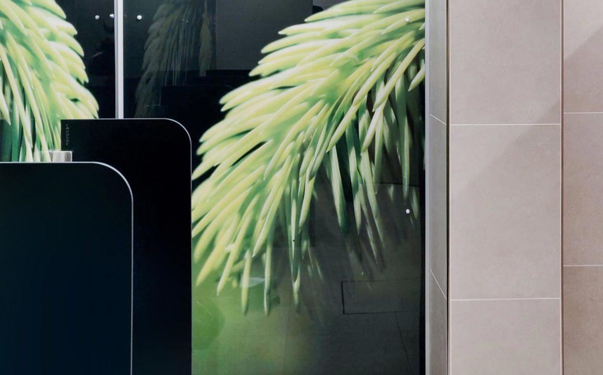 WC-tilassa on kaksi mustaa pisuaarin Ujo-väliseinää. WC-tilan takaseinässä on kuvapaneeli, jossa näkyy vihreä kuusenkerkkä aiheinen kuva.