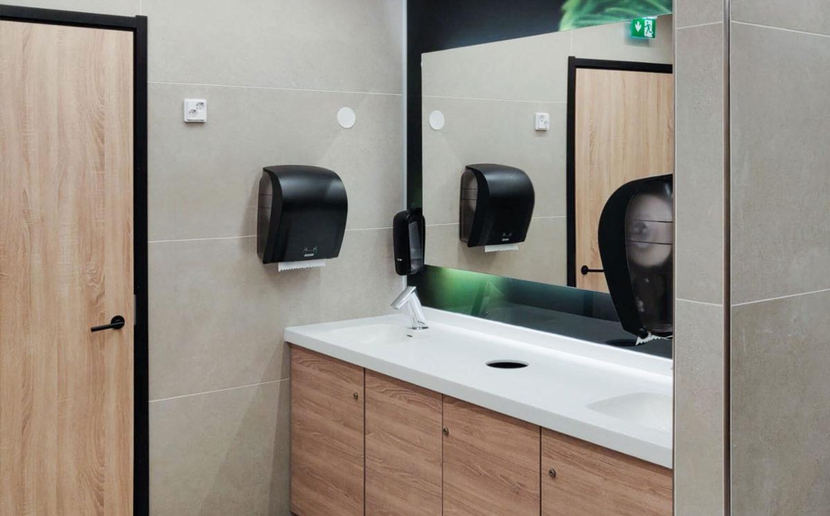 Vessassa on peilikaappi, valkoinen allastaso ja Conti-hana. Mustat paperi ja saippua-annostelijat on kiinnitetty vaaleaan seinään.
