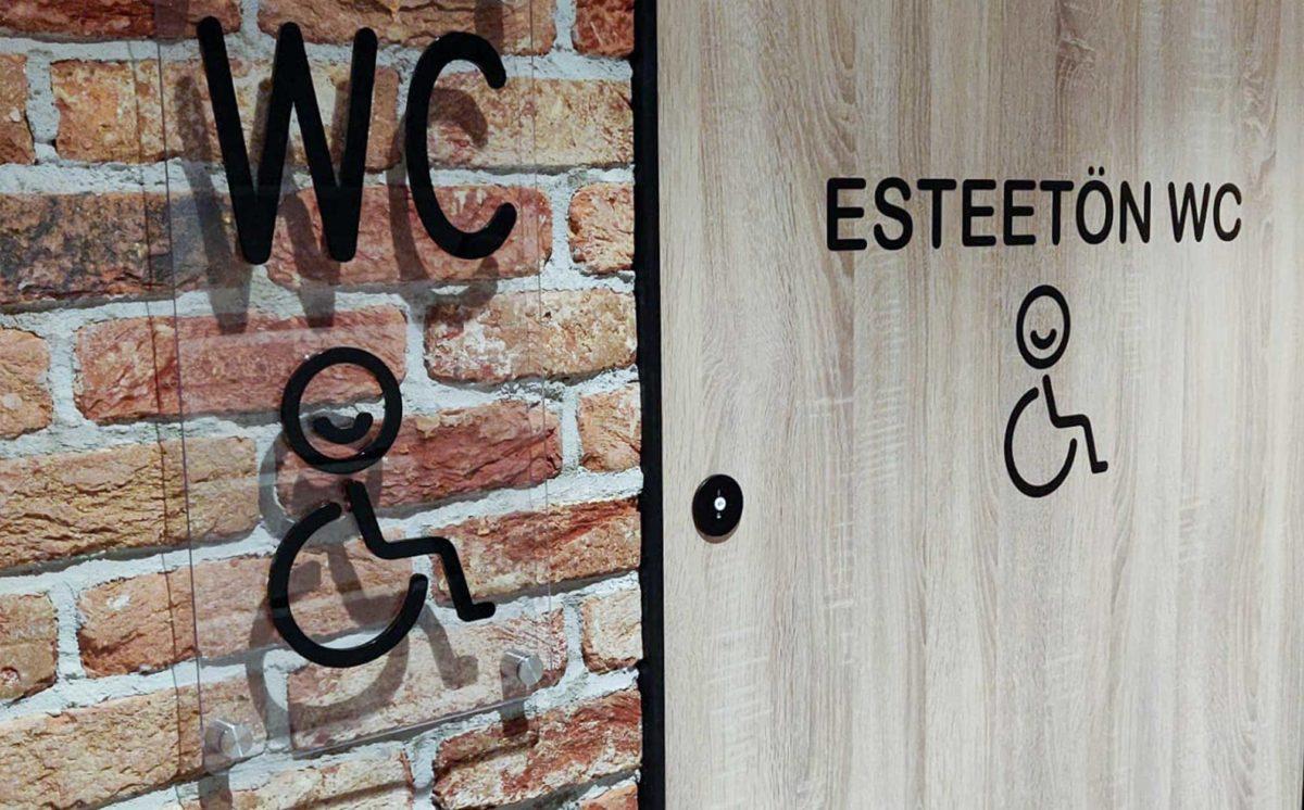 Rouheaan tiiliseinään on kiinnitetty läpinäkyvä WC-kyltti pyörätuoli symbolilla. Vieressä on vessan ovi jossa lukee, esteetön WC.