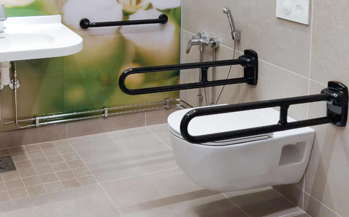 Inva WC:ssä on yksi valkoinen seinä-WC, jonka sivuilla on kaksi mustaa Inva-WC:n tukikaidetta. WC-tilan takaseinässä on yksi musta tukikahva.
