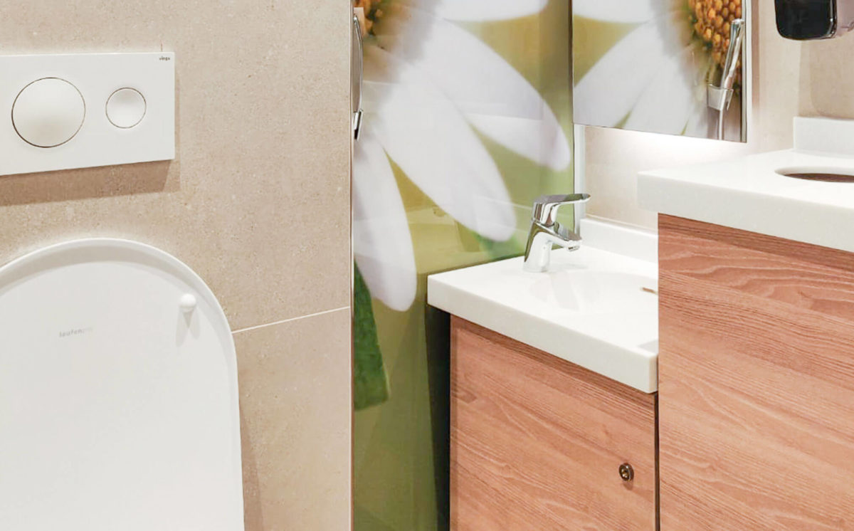 WC-tilan sivuseinässä on suuri kukkakuvio. Seinällä on yksi peilikaappi ja kulmassa bidee suihku. Matalassa valkoisessa allastasossa näkyy yksi hana, allaskaapit ovat puun sävyiset. Valkoinen WC-istuimen kansi näkyy etualalla.
