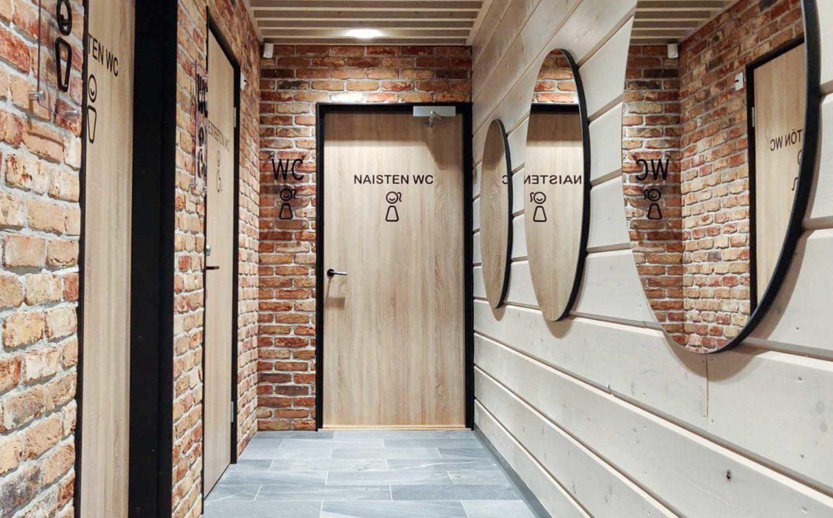 Käytävässä on kolme WC-opasteilla merkittyä ovea. Vastakkaisella seinällä on kolme pyöreätä peiliä. Päätyseinän vaaleassa puun sävyisessä ovessa lukee naisten-WC.