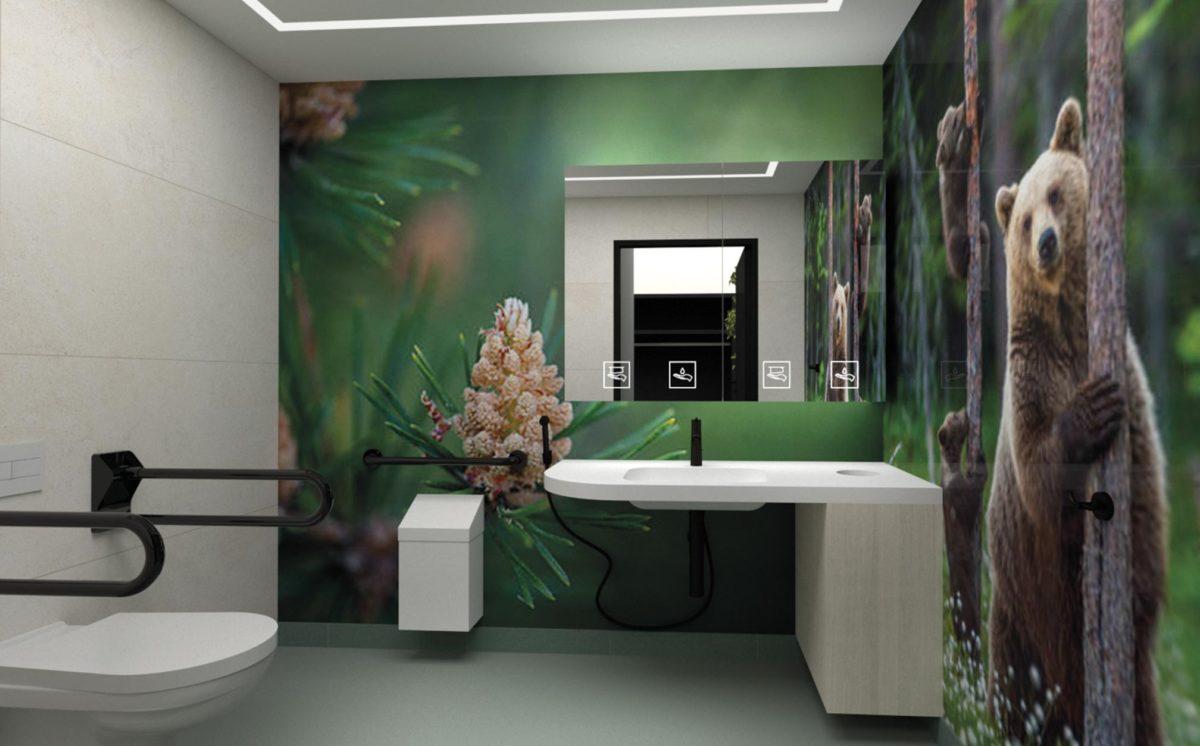 3d-mallinnos inva-WC:stä. Seinällä peilikaappi ja kuvvitus suopursuista ja karhusta metsässä pitelemässä kiinni puun rungosta. WC-tilassa on valkoinen WC-istuin, allastaso ja roska-astia. Inva-tukikahvat ovat mustat.