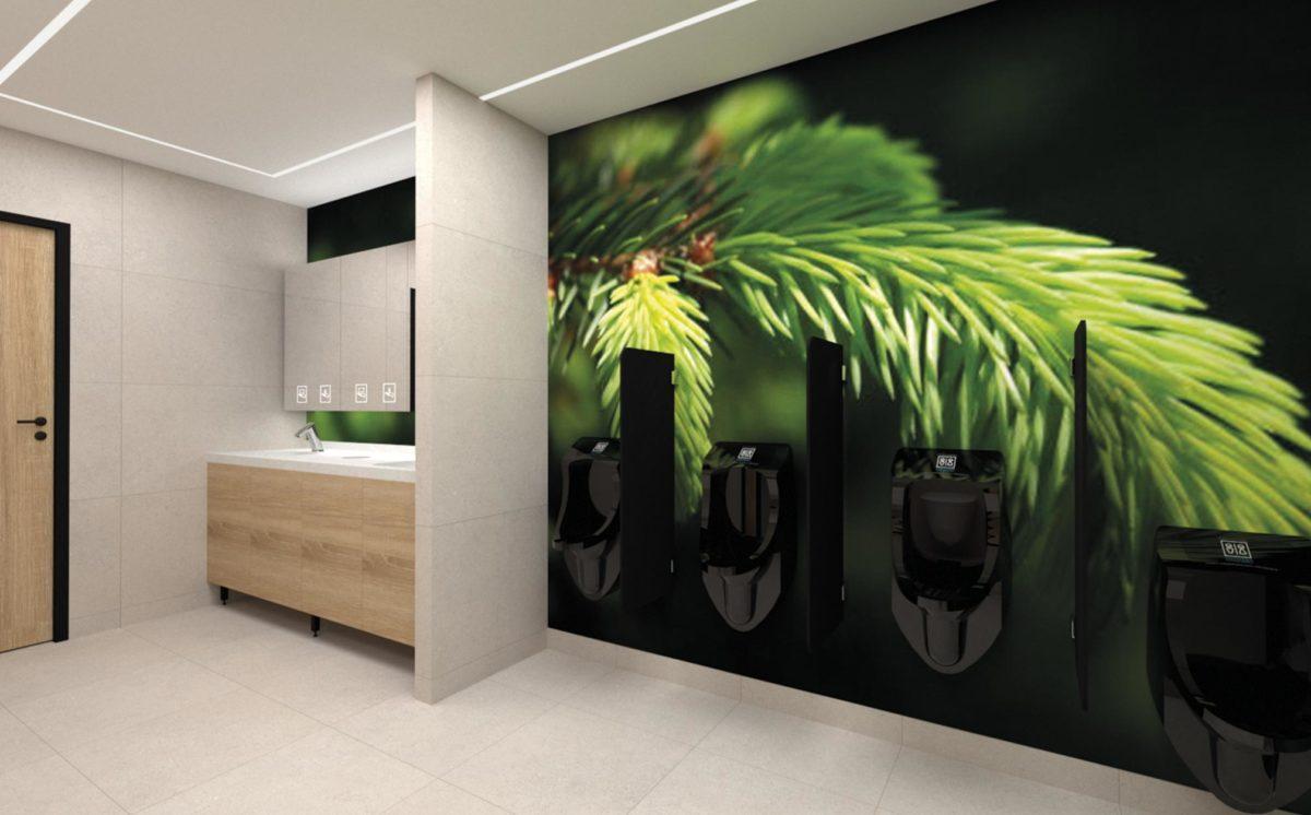 Miesten WC-tilassa allastaso, jonka päällä valaistu peilikaappi. Seinällä on iso kuva kuusenkärkästä, jonka edessä on neljä mustaa pisuaaria. Yksi pisuaareista on alempana, lasten korkeudella. Katossa epäsuora valo.
