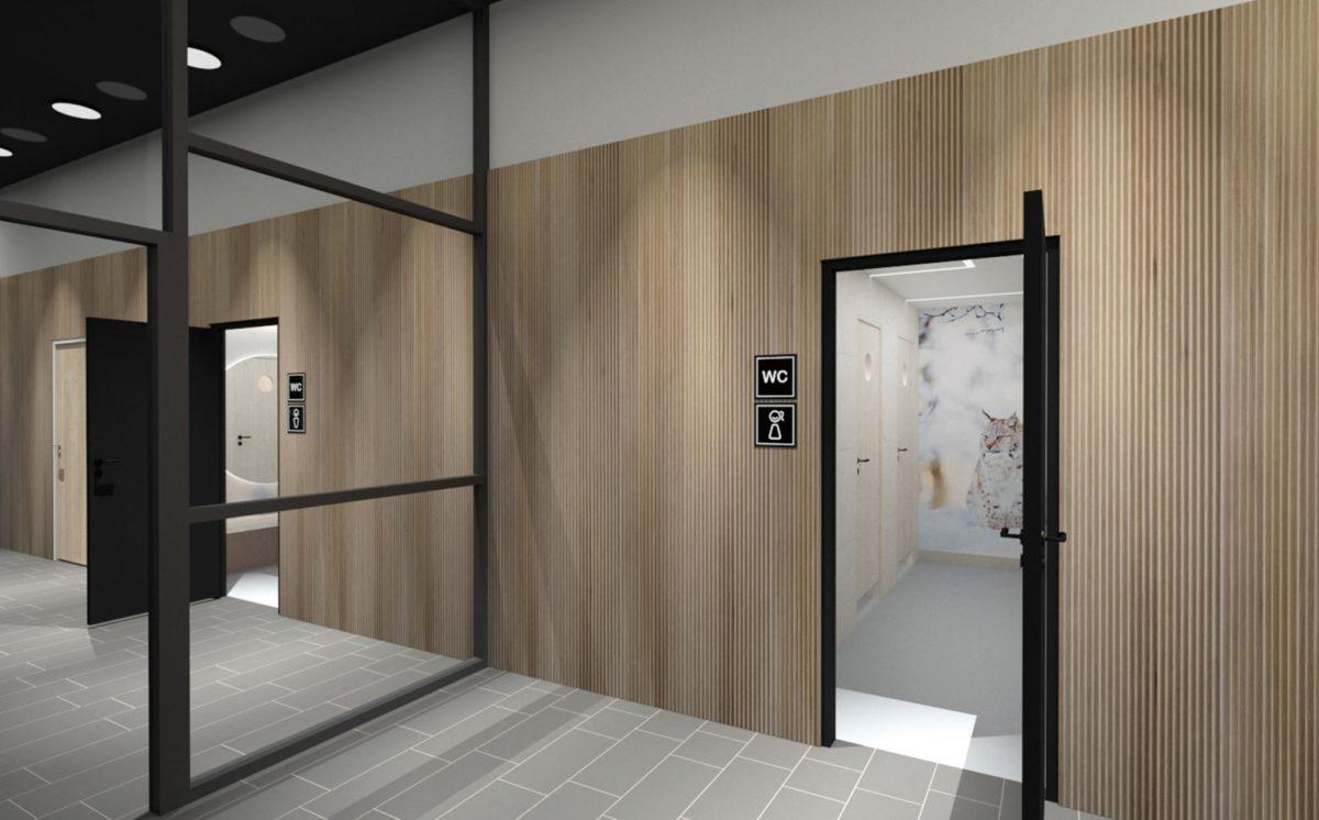 3D-mallinnoskuvassa on aula, josta pääsy WC-tiloihin. Aulan seinä on Siparilan sormipaneelia. Seinällä WC-opasteet naisten ja miesten vessoihin.