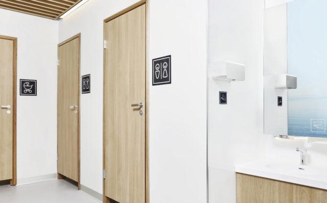 WC-tilassa kolme kiinniolevaa vessan ovea, peilikaappi, käsienkuivaaja ja allastaso. Seinällä WC-opasteet.