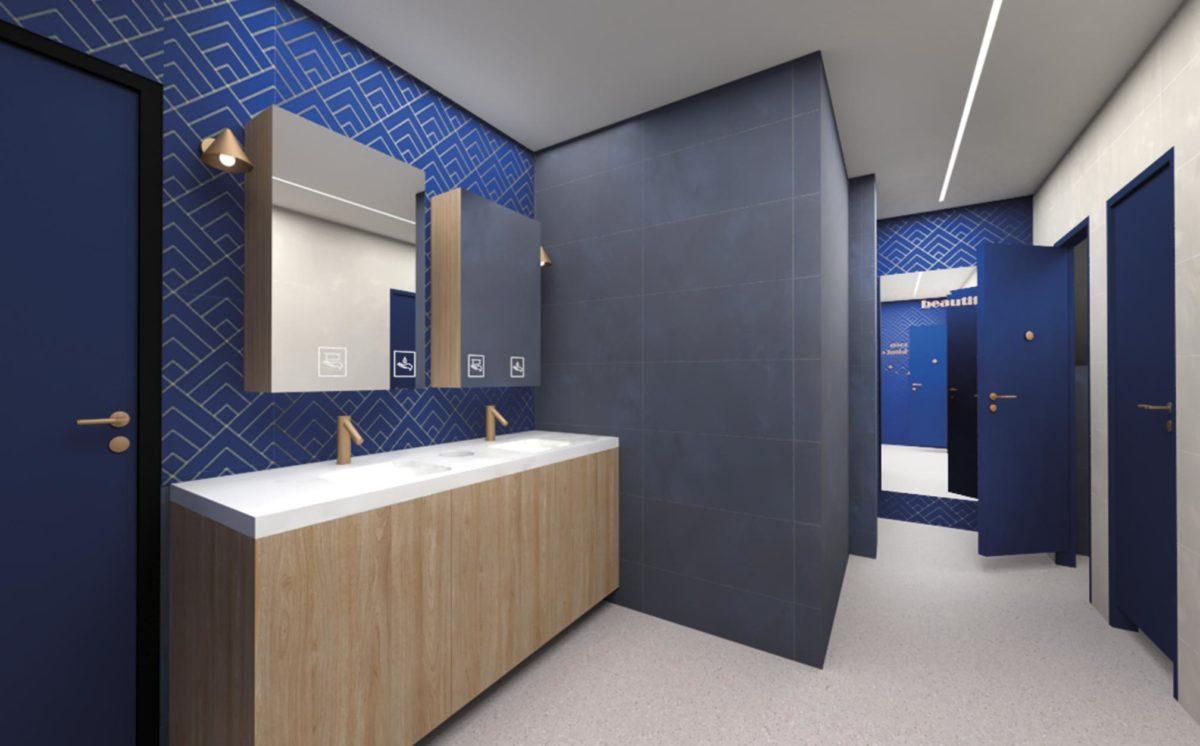 WC-tilassa on graafinen sini/kulta-kuvioinen seinäpinta. Seinällä on kaksi peilikaappia. Allastasossa on kaksi pesuallasta ja kultaiset hanat. WC-eriöiden ovet ovat kirkkaan siniset. Katossa on epäsuora valo.