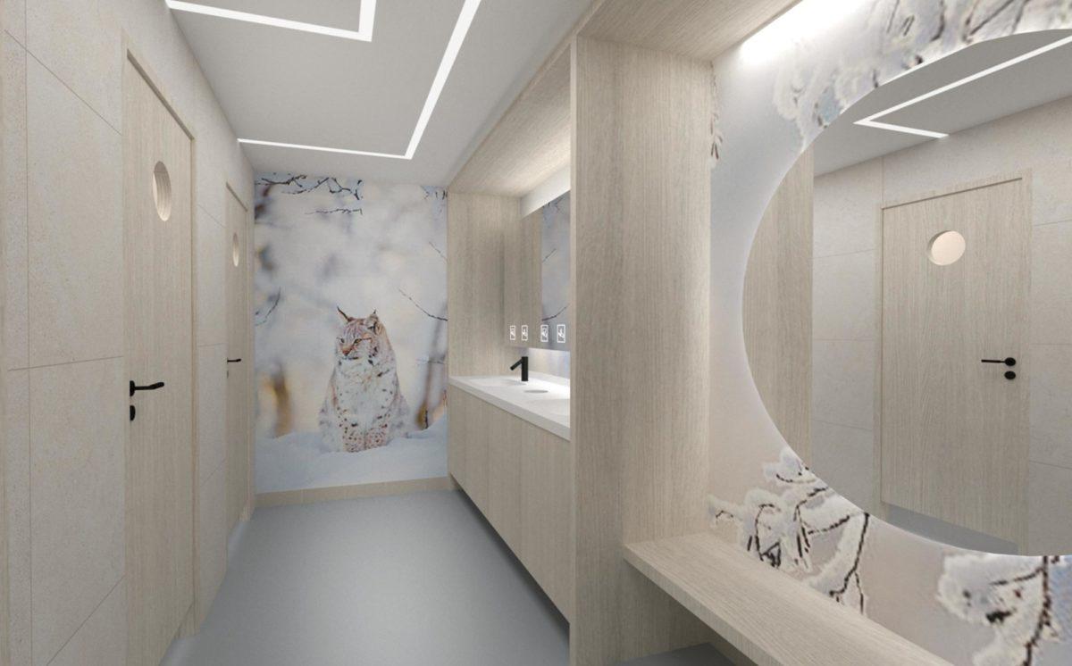 WC-tila on vaalea, seinällä kuvitus ilveksestä ja talvisesta luonnosta. 3d-mallinnoksessa näkyy WC-eriöiden ovet, peilikaappi, allastaso ja iso pyöreä peili, jonka edessä on penkki. Katossa on epäsuora valo.