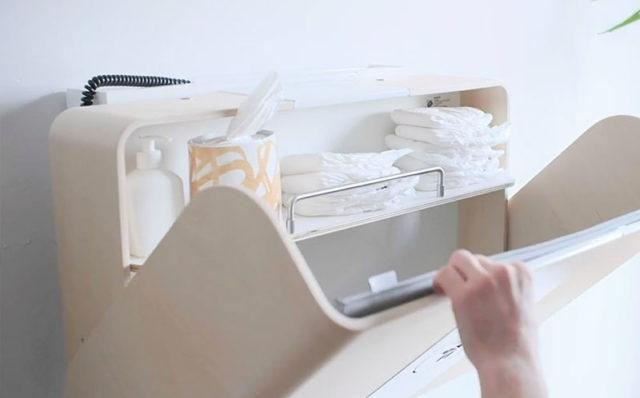 Vaaleaa puunsävyistä lastenhoitopöytää avataan. Hoitopöydän ylähyllyllä on vaippoja, käsipyyhkeitä ja käsidesiä. Novosan Hiiwi-hissi Timkid-lastenhoitopöytään.