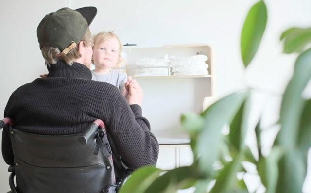Novosan Hiiwi-hissi Timkid-lastenhoitopöytään. Mies istuu pyörätuolissa vauva sylissään. Taustalla näkyy vauvan hoitopöytä.